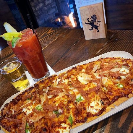 Thai Chicken Flatbread. --Herbed Flatbread, Spicy house-made Thai Chili Sauce, Mozzarella, Chicken, Red Onion, Cream Cheese, and Asparagus. Topped with Crispy Wontons.