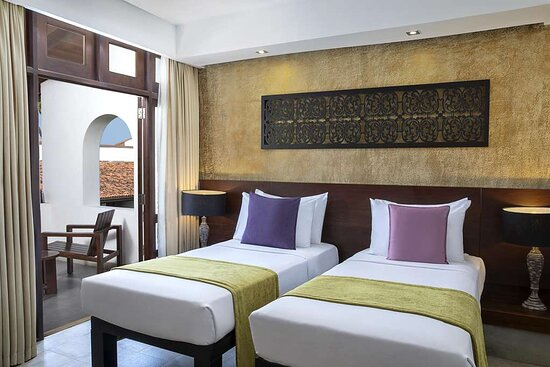 Interior view of twin beds in Avani Courtyard View Room bedroom with balcony view