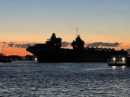 The aircraft carrier HMS Queen Elizabeth leaving Portsmouth at dusk as it sets out on its first 28 week deployment
