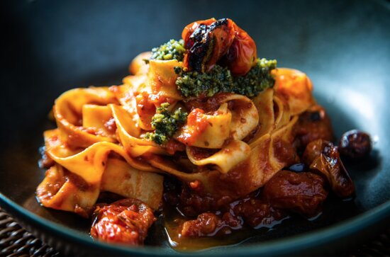 Homemade tagliatelle with tomatoes and pesto