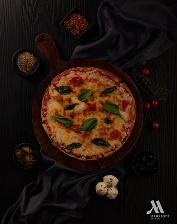 Handrolled thin crust pizza with choice of sauce and toppings from local Indiana or Chicken tikka, to classical pepperoni or margherita, cooked at site in the Pizza Oven at Okra