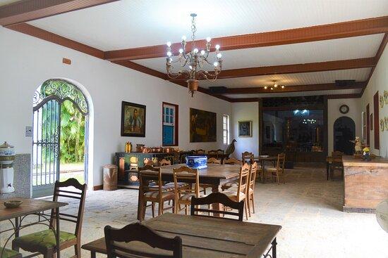 Rio das Flores, RJ: Um dos restaurantes do Hotel do Café com a destilaria da Cachaça do Catito ao fundo