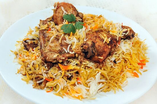 Chicken Biryani (GF) Aged extra long aged Basmati rice from the foothills of Himalaya's, cooked over chicken meat on the bone marinated in yogurt and spices, then richly flavored with Spanish Saffron.