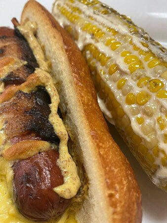 Sheridan, MT: The Gut Buster-- a polish sausage wrapped in bacon and grilled.  Add sauerkraut, relish, onions...