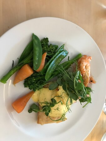 Smoked Haddock and Salmon Fillets with King Prawns Served with a light mustard dill hollandaise sauce, vegetables and new potatoes.