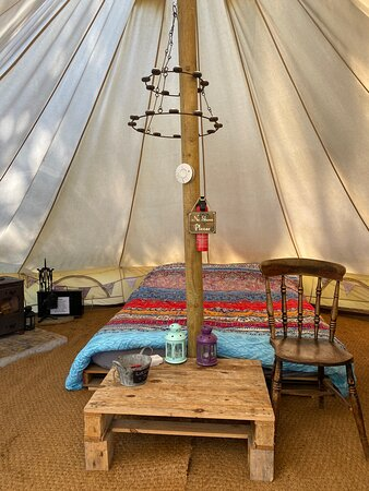 Secluded Bell tent , furnished with a king size bed and bedding included. Log burner , outdoor fire pit and BBQ grill, electric kettle and 2 ring electric hob, fairy lights and fire starter pack. 2 x Single beds with bedding as an optional extra. Well behaved dogs welcome