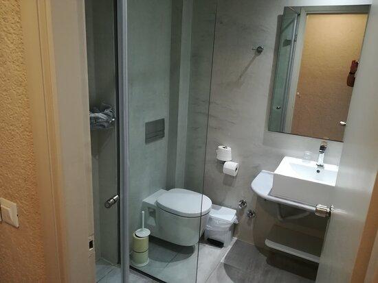Das kleine Bad mit schlechter Lüftung so wie zwei Seifenspendern ,Fön ,Dusche.