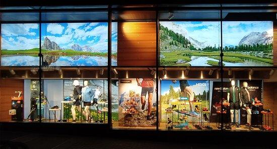 La sera, le vetrine della Cooperativa di Cortina si illuminano dei colori della natura che ci circonda.