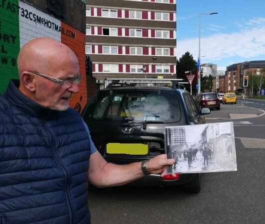 Belfast Black Taxi Murals and Peace Walls with the Original Drivers: Our driver Brenton showing us images of how this area of the Falls Rd looked in the 70s