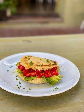 Arepa rellena con tomates y palta