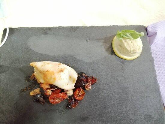 Calamaro ripieno su pomodorini confit, accompagnati da un fresco gelato al basilico e lime