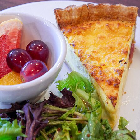 A slice of quiche Lorraine served with greens and fruit.