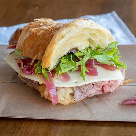 1/2 seared roast beef croissant with Swiss cheese, pickled onion, and greens.