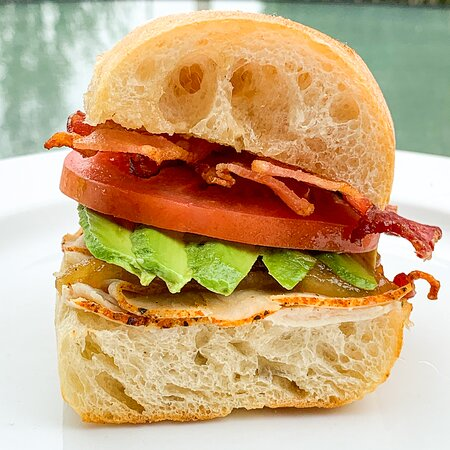 1/2 turkey bacon avocado sandwich. Piled high on a ciabatta roll with caramelized onion jam and tomatoes.