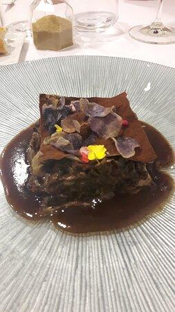Rabo de vaca deshuesado cocinado en vino tinto con cacao y patatas violeta.