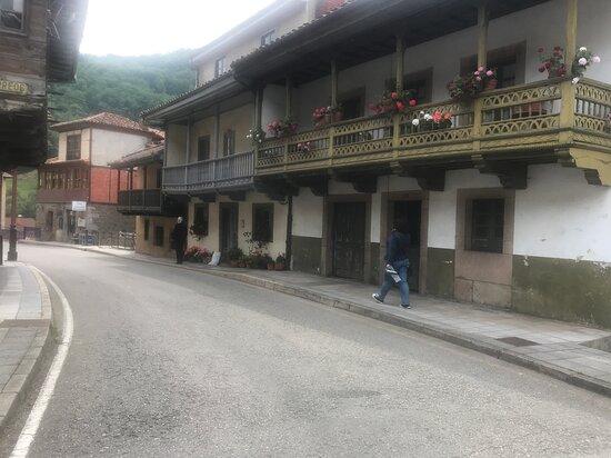 La calle es la carretera y en ella aparecen bonitos edificios. El granate, al fondo, es el que habilitar el bar