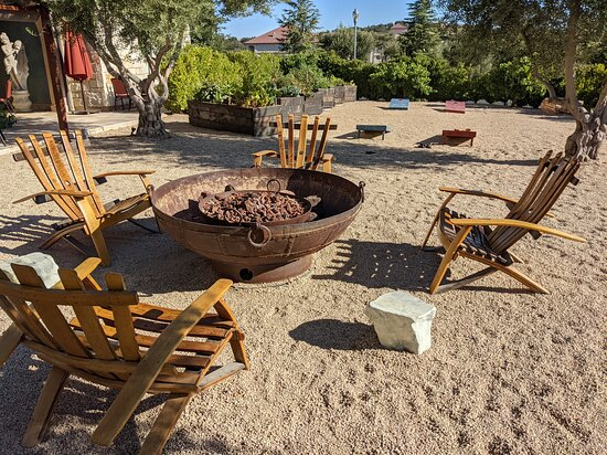 Adirondack chairs and firepits are around the property