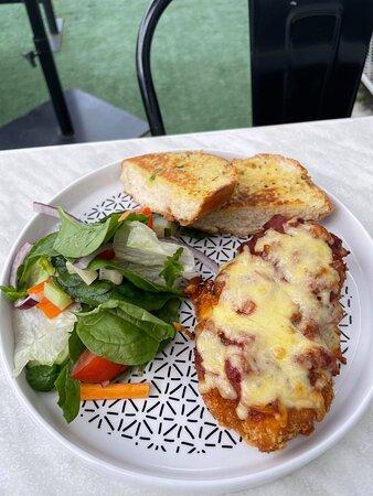 Chicken Parmi served with salad and garlic bread