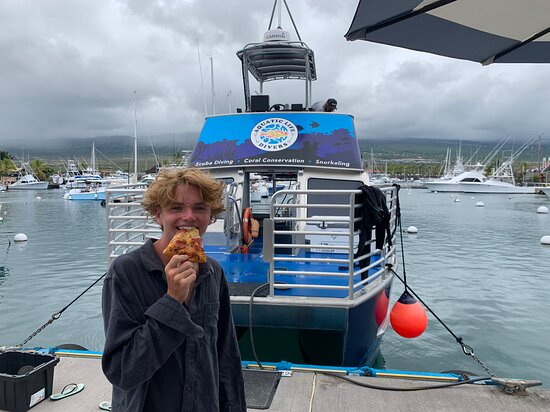 Moondance student eating Hawaiian pizza right after being certified as an Open Water diver by Aquatic Life