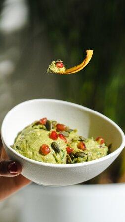 Guacamole 100 % Ecológico con granada y pipas de calabaza acompañado de chips de platano.