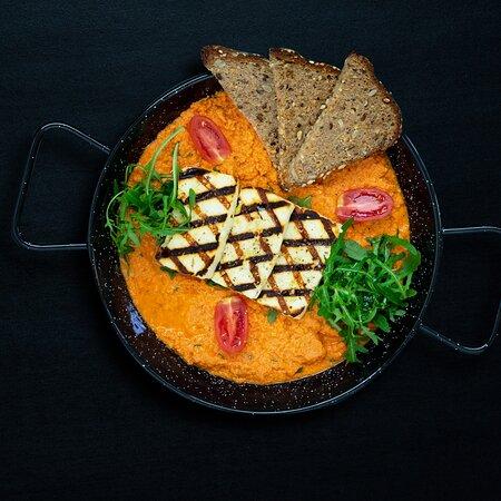 Kayiana (V)        A blend of slow cooked tomato sauce with eggs, rucola and grilled halloumi, served with toasted multigrain bread   Μείγμα από σάλτσα ντομάτας και αυγά, ρόκα, χαλούμι στη σχάρα και πολύσπορο ψωμί  Кайана - нежный омлет (V)    Смесь из приготовленного на медленном огне томатного соуса, яиц, рукколы и копченого халуми, жареного на гриле