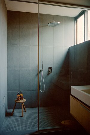 Ensuite bathroom with heated stone floors, oversized rainfall shower and a view of treetops.