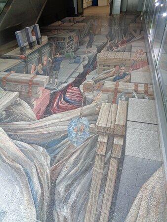 Przy tym drugim wejściu podłoga udekorowana jest trójwymiarowym malowidłem. Przedstawia ono baśniową pracownię hutniczą autorstwa Ryszarda Paprockiego z 2013 roku .