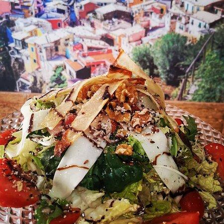 Ensalada templada con bakon salteado y caliente, frutos secos, queso provolone, parmigiano, balsamico de Modena, tirtitas de crepe casero