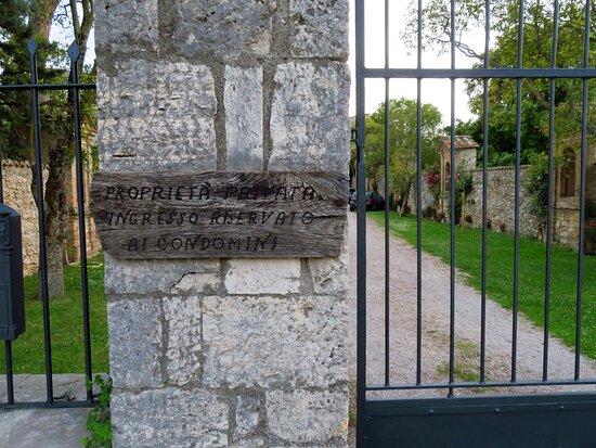 Accanto al cancello chiuso questo cartello in legno avvisa che trattasi di proprietà privata con accesso riservato ai condomini