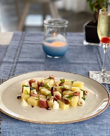 Modern Greek Dining Starter Koukouritsa (Potatoes, Spicy Feta Mousse, Truffle, Nouboulo, Toasted Hazelnuts)