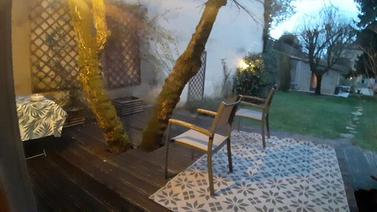 Outdoor wooden patio with table n chairs.