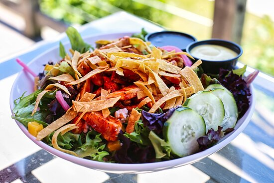 Huli Huli Chicken Salad - Zesty honey glazed chicken dusted with citrus grill seasoning on a bed of chopped field greens with mango, pickled red onion, cucumber, fresh crumble goat cheese and crisp wonton threads.