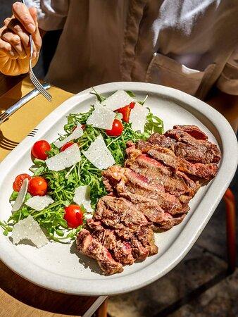 TAGLIATA TOSCANA Entrecôte de bœuf 350g, cuite au charbon de bois et servie avec une salade de roquette, tomates cerises et copeaux de Parmigiano Reggiano AOP, comme à Florence