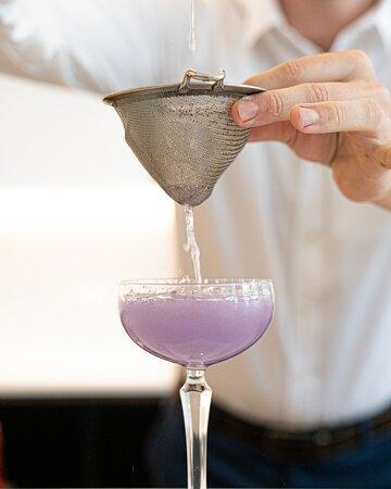 Ms Margot's specialty cocktail - Debbie After Dark made with Ink Gin, lemon juice and Crème De Violette.