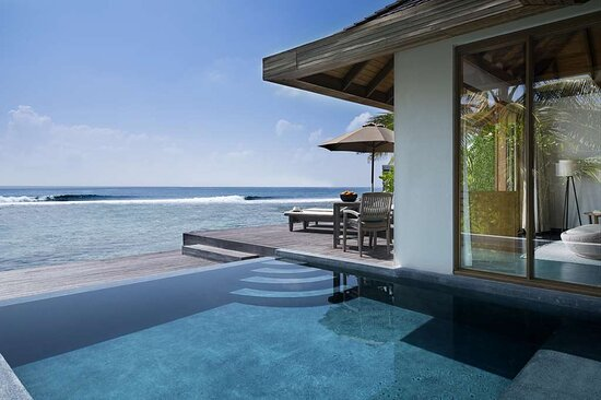 Exterior view of private swimming pool on Ocean Pool Bungalow deck with sun-loungers and lagoon view