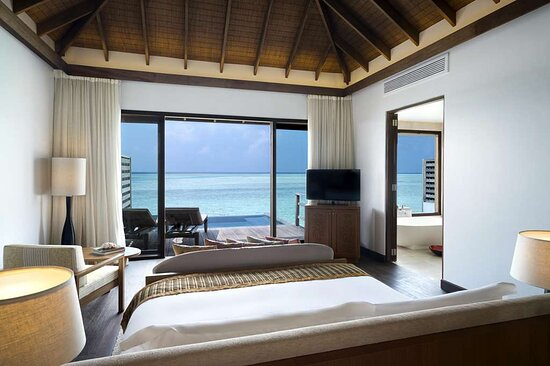 Interior view of bedroom in Deluxe Over Water Pool Bungalow with view of bathroom and sun-loungers on pool deck