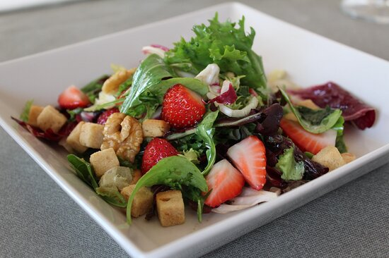 Green leafy salad with nuts, strawberries and croutons.