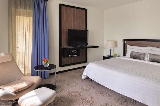 Bedroom area with sofa and TV in Avani Junior Suite