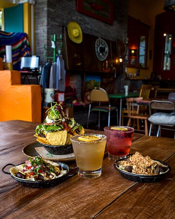 An assortment of nachos, a mushroom taco, and the brisket taco, accompanied by a couple of cocktails.