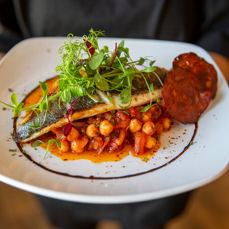 Pan-fried fillet of sea bass, spiced tomato, Mediterranean vegetable and chickpea stew, chorizo crisp
