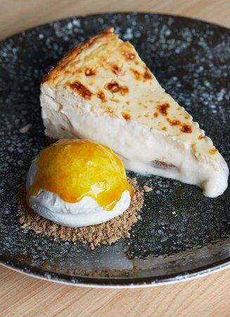 Tarta de queso horneada con helado de yogur y coulis de maracuyá.