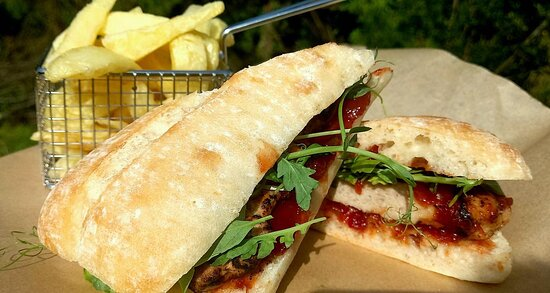 Fuel flame cooked pork rib steak sandwich on ciabatta bread with rocket and tomato and chilli jam.