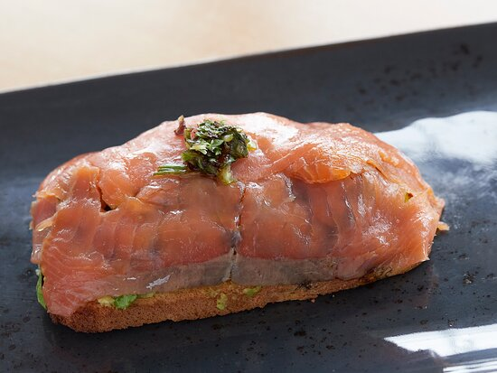 Tosta de salmón ahumado sobre una base de aguacate y lechuga.