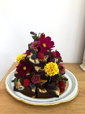 Pirámide de Cheesecake Brownies con flores comestibles y fruta fresca.