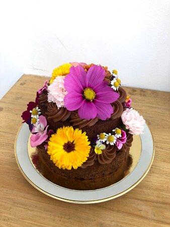 """""""El Pastel de Chocolate"""" personalizado con efecto de dos pisos y flores comestibles."""