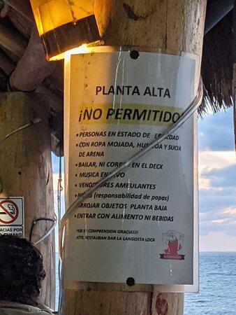 Notice on balcony support post at La Langosta Loca Restaurant.
