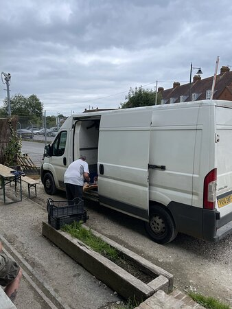 The Goods Shed butcher cutting up raw meet on the floor of a dirty van.