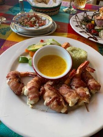 Bacon wrapped shrimp with passionfruit sauce.