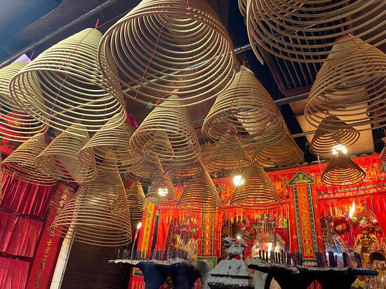 Giant rings of incense hang overhead inside a traditional temple on Tai Ping Shan Street.
