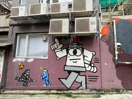 Several local and international artists have made their mark on the Tai Ping Shan Street walls. Many of the works were commissioned for the annual HKWALLS event. It pays to look down the lanes  running off Tai Ping Shan Street, where you'll find more works like this cartoon robot by UK based artist, 45RPM